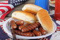 Patriotic hot dogs grilled hotdogs and buns on a plate with american flag in background Royalty Free Stock Image