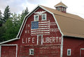 Patriotic red barn with painted american flag and in god we trust Stock Photo