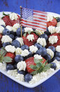 Patriotic red, white and blue berries with fresh whipped cream stars and USA flag.