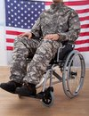 Patriotic Soldier Sitting On Wheel Chair Against American Flag Royalty Free Stock Photo