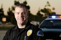 Patrol cop a smiling police officer standing in front of his car Royalty Free Stock Image