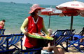 Pattaya thailand vendor selling food on beach woman fresh fruits displayed in a tray walks along hoping to make sales to Stock Images