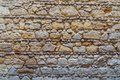 Pattern of yellow and gray decorative grunge weathered uneven stone wall surface Royalty Free Stock Photo
