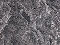 Patterns cracks and shapes emerge from this close up portion of black solidified lava on the island hawaii Royalty Free Stock Images