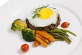 Patty, cooked vegetables and fried eggs Stock Image