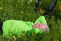 Pause of a cyclist senior lying in the grass making Royalty Free Stock Photos