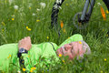 Pause of a cyclist senior lying in the grass making Stock Images