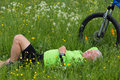 Pause of a cyclist senior lying in the grass making Stock Photography