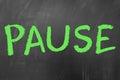 Pause word written wth green chalk on school blackboard Stock Photo