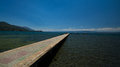 Paved gangplank over lake ohrid the leads the to a swimming spot in clear blue water macedonian hot spot Stock Images