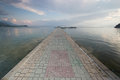 Paved gangplank over lake ohrid the leads the to a swimming spot in clear blue water macedonian hot spot Stock Image
