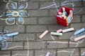 Pavement chalk drawings box of chalks on or sidewalk with drawing of flower Royalty Free Stock Image