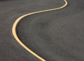 Pavement curved lane with single yellow line Royalty Free Stock Images