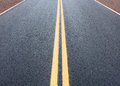 Pavement detail view of highway with yellow double line Royalty Free Stock Photography