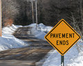 Pavement ends sign indicating the end of the blacktop road changing to rough gravel and low maintenance Stock Photo