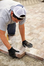 Paver stone landscaping concept man worker or trade putting down stones vertical Royalty Free Stock Images