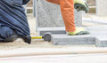 Paver working on knees construction worker placing stone tiles in sand for pavement Stock Images