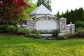 Pavilion with stone front fence horizontal evening view photo of a new white surround by evergreens japanese red maple tree and Royalty Free Stock Image