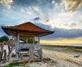 Pavillion traditionnel sur la plage de coucher du soleil Image stock