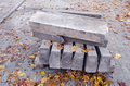 Paving concrete blocks in pile for repair of pavement and autumn leaves Royalty Free Stock Image