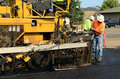 Paving machine asphalt laying down a fresh layer of on a new road interchange project Stock Photography