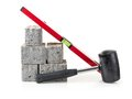Paving props concrete pavement blocks with mallet and spirit level ahot on white Stock Photos