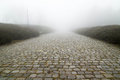 Paving stone road with fog ahead Stock Photos