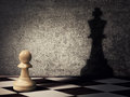 Pawn aspiration chess piece casting a shadow of a king on a concrete wall business aspirations and leadership concept magical Stock Images