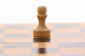 Pawn on a wooden chessboard over white Stock Photography