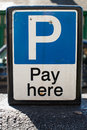 Pay here parking sign in a lot Stock Photos