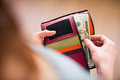 Paying in cash for a product or service over the shoulder view of young woman taking us dollar bills out of her wallet shallow dof Royalty Free Stock Images