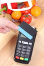 Payment terminal with contactless credit card, fruits and vegetables, cashless paying for shopping Royalty Free Stock Photo