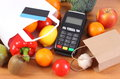 Payment terminal, contactless credit card, paper shopping bag with fruits and vegetables Royalty Free Stock Photo