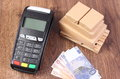 Payment terminal, currencies euro and wrapped boxes on wooden pallet, concept of paying for products Royalty Free Stock Photo