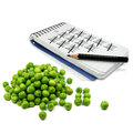 Pea counter a pile of peas in front of a notebook and pen symbol for a control freak in germany Stock Photography