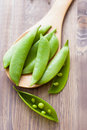 Pea pods on spoon wooden background Stock Image