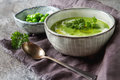 Pea soup puree in an old plate with parsley decoration. Stone sl Royalty Free Stock Photo