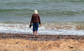 Peace of being alone by the sea an elderly lady standing looking out to she has her shoes in her hand and is on her own peacefully Stock Image