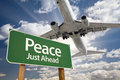 Peace green road sign and airplane above with dramatic blue sky clouds Royalty Free Stock Photos