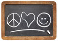 Peace love and happiness symbols white chalk sketch on a vintage slate blackboard Royalty Free Stock Photography