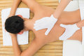 Peaceful brunette enjoying an exfoliating back massage in the health spa Stock Photo