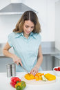 Peaceful brunette woman cutting vegetables standing in her kitchen at home Stock Image