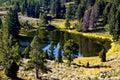 A small, calm mountain lake reflecting its surroundings` beautiful fall colors Royalty Free Stock Photo