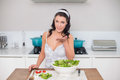 Peaceful pretty brunette preparing healthy salad blowing kiss in bright kitchen Stock Photos