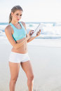 Peaceful slender blonde in sportswear using tablet on a sunny beach Stock Image