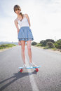 Peaceful trendy woman balancing on her skateboard a deserted road Royalty Free Stock Photo