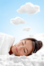 Peaceful woman sleeping on a cloud and having sweet dreams Stock Image