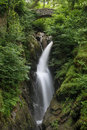 Peaceful woodland flowing waterfall in the Lake District.