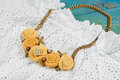 Peach-colored handicraft necklace lies on lace dress Royalty Free Stock Photo