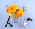 Peach compote in glass bowl with blueberries and vanilla fork Royalty Free Stock Photo